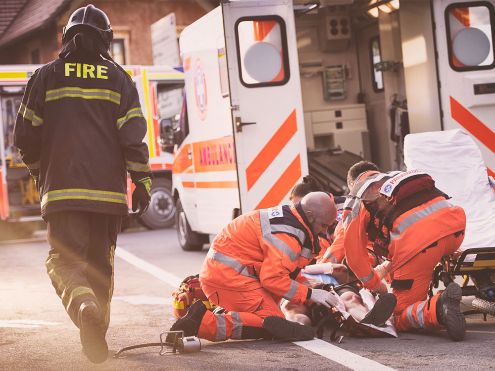 paramedics working on injured person while firefighter walks by
